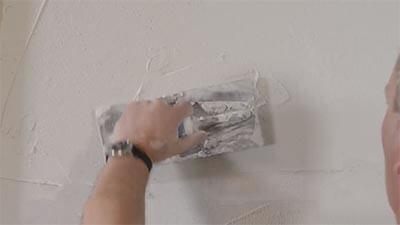 Gebruik een spackmes om de muur te egaliseren